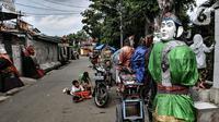 Anak-anak bermain dekat ondel-ondel di Kramat Pulo, Jakarta, Rabu (10/2/2021). Pendapatan sejumlah sanggar ondel-ondel di Kramat Pulo merosot karena larangan menggelar pesta pernikahan atau sejenisnya selama pandemi. (merdeka.com/Iqbal S. Nugroho)