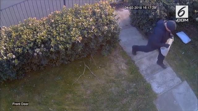Aksi pencurian paket di halaman rumah oleh seorang pria.