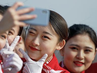 Sejumlah wanita berswafoto di sela penyambutan para peserta Kongres Rakyat Nasional di Beijing, China, Senin (4/3). Para wanita berparas cantik tersebut bertugas menyambut para tamu yang menghadiri kongres. (AP Photo/Andy Wong)