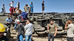 Orang-orang berkumpul di sekitar reruntuhan dua kereta yang bertabrakan di distrik Tahta di provinsi Sohag, sekitar 460 km (285 mil) selatan ibu kota Mesir, Kairo (26/3/2021). Tabrakan maut dua kereta di Mesir menewaskan sedikitnya 32 orang dan melukai sekitar 165 orang. (AFP)