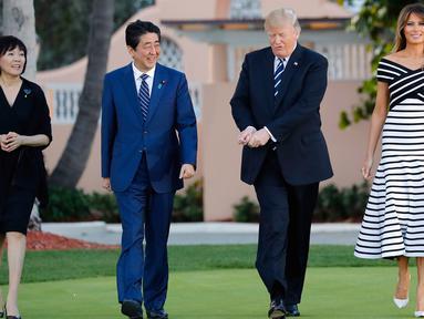 Presiden AS, Donald Trump didampingi Ibu Negara, Melania Trump berjalan bersama Perdana Menteri Jepang, Shinzo Abe dan istrinya Akie Abe untuk jamuan makan malam dalam pertemuan di Resor Mar-a-Lago, Florida, Selasa (17/4). (AP/Pablo Martinez Monsivais)