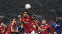 Striker Manchester United (MU) Edinson Cavani menyundul bola dalam laga kontra Chelsea pada pekan keenam Liga Inggris di Old Trafford, Sabtu (24/10/2020). (Michael Regan/Pool via AP)