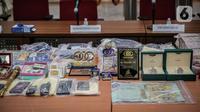 Sejumlah barang bukti diperlihatkan saat rilis kasus dugaan investasi ilegal E-Dinar Coin (EDC) Cash.di Bareskrim Polri, Jakarta, Kamis (22/4/2021). Para tersangka dijerat atas dugaan tindak pidana penipuan, penggelapan, dan tindak pidana pencucian uang (TPPU). (Liputan6.com/Faizal Fanani)