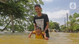 Warga melintasi banjir di Desa Sukalaksana Kabupaten Bekasi, Jawa Barat, Senin (22/02/2021). Jebolnya tanggul Sungai Citarum ini disebabkan oleh debit air yang tinggi. (Liputan6.com/Herman Zakharia)