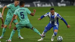 Pemain Espanyol, Raul de Tomas, berusaha melewati pemain Real Madrid, Raphael Varane, pada laga La Liga di Stadion Cornella-El Prat, Minggu (28/6/2020). Real Madrid menang 1-0 atas Espanyol. (AP/Joan Monfort)