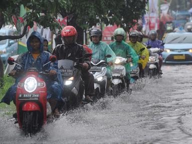 Pengendara bermotor melewati banjir di Jalan Cinere Raya (depan Mall Cinere), Depok, Jawa Barat, Minggu (31/3). Banjir terjadi akibat sistem drainase yang buruk. (merdeka.com/Arie Basuki)