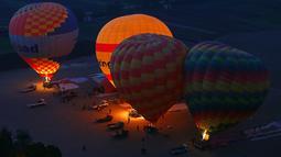 Sejumlah balon udara panas melakukan persiapan sebelum terbang membawa wisatawan di Luxor, Kairo, Mesir (13/12). Di kota Luxor, beberapa situs-situs kuno masih berdiri kokoh. (Reuters/Amr Abdallah Dalsh)