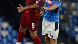 Striker Liverpool, Roberto Firmino, berebut bola dengan pemain Napoli, Kostas Manolas pada matchday pertama Grup E Liga Champions di Stadion San Paolo, Selasa (17/9/2019). Napoli menundukkan Liverpool 2-0. (AP/Gregorio Borgia)