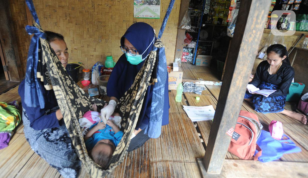 Petugas medis Puskesmas Cisimeut Bidan Pite memeriksa kesehatan bayi saat Posyandu keliling di Kampung Baduy Luar Gazebo, Kanekes, Banten, (Rabu (27/01/2021). Setiap bulannya Bidan Pite berkeliling Baduy Luar sepanjang sekitar 14 km pulang pergi berjalan kaki. (merdeka.com/Arie Basuki)