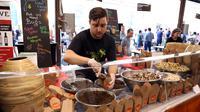 Penjual makanan berbahan dasar serangga menyiapkan pesanan di Sydney, Australia, Sabtu (28/4). Belakangan ini, serangga dijadikan rujukan sebagai pengganti protein yang berasal dari ayam dan sapi. (AFP FOTO / ANDREW MURRAY )