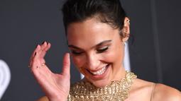Aktris Gal Gadot tersenyum saat tiba menghadiri pemutaran perdana film produksi Warner Bros 'Justice League' di Teater Dolby di Hollywood, California, AS (13/11). Gal Gadot tampil cantik dengan gaun emas berkilauan. (AFP Photo/Robyn Beck)