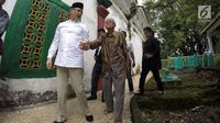 Saifudin Aswari menggandeng seorang kakek saat ziarah ke makam Sultan Mahmud Badaruddin di Palembang, Sumsel, Jumat (26/1). Aswari menggandeng Wali Kota Pangkalpinang M Irwansyah sebagai pasangan bakal calon Pilkada Sumsel 2018. (Liputan6.com/Aswari)