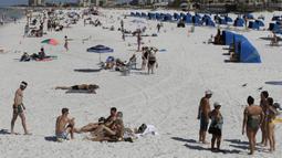 Pengunjung menikmati Clearwater Beach di Florida, Amerika Serikat, Rabu (18/3/2020). Virus corona COVID-19 sudah menyebar ke seluruh wilayah Amerika Serikat dengan jumlah kasus sebanyak 5.359 dan menewaskan 100 orang. (AP Photo/Chris O'Meara)