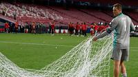 Kiper Bayern Munchen, Manuel Neuer membawa jaring gawang saat merayakan timnya meraih trofi Liga Champions usai mengalahkan PSG pada pertandingan final di stadion Luz di Lisbon (23/8/2020). Munchen menang tipis atas PSG 1-0. (AFP/Lluis Gene)