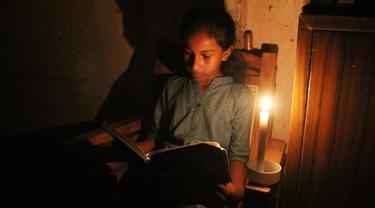 Seorang gadis membaca dengan bantuan lilin di tengah pemadaman listrik di Kolombo, Sri Lanka (17/8/2020). Sri Lanka mengalami pemadaman listrik berskala nasional pada Senin (17/8) karena kerusakan teknis di sebuah pembangkit listrik di Kerawalapitiya. (Xinhua/A. Hapuarachchi)