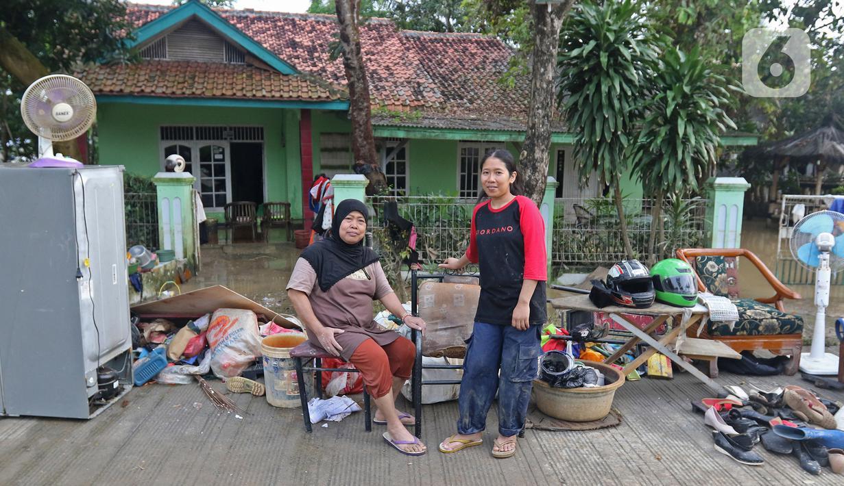 Keluarga ibu Haji Mamah Rusmahwati berpose di depan kediamannya Desa Sumber Urip Pebayuran, Kabupaten Bekasi, Jawa Barat, Senin (22/2/2021). Banjir merenda keluarga tersebut merapikan barang-barang dan bersihkan rumah yang sudah surut. (Liputan6.com/Herman Zakharia)