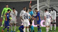 Wasit Jesus Gil Manzano memberikan kartu merah kepada gelandang Real Madrid, Casemiro (kedua dari kiri) saat melawan Barcelona dalam laga lanjutan Liga Spanyol 2020/2021 pekan ke-30 di Alfredo di Stefano Stadium, Madrid, Sabtu (10/4/2021). Real Madrid menang 2-1 atas Barcelona. (AFP/Javier Soriano)
