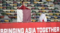 Seorang suporter membawa bendera negara saat mendukung Timnas Qatar saat laga Piala Asia 2019 di Zayed Sports City Stadium, Abu Dhabi (17/1/2019). (AFP/Khaled Desouki)