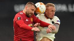 Bek Manchester United, Luke Shaw (kiri) berduel udara dengan bek AS Roma, Rick Karsdorp dalam laga leg pertama semifinal Liga Europa 2020/2021 di Old Trafford Stadium, Manchester, Kamis (29/4/2021). Manchester United menang 6-2 atas AS Roma. (AFP/Paul Ellis)
