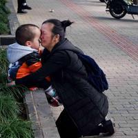 Tak mampu menanggung biaya rumah sakit untuk perawatan anaknya, ibu ini terisak di depan rumah sakit. (Sumber Foto: NextShark)