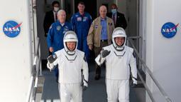 Astronot NASA Douglas Hurley (kiri) dan Robert Behnken bersiap untuk misi peluncuran roket SpaceX Falcon 9 di Cape Canaveral, Florida, Sabtu (30/5/2020). Kedua astronot akan tinggal di ISS selama satu hingga empat bulan, bergabung dengan para astronot lainnya. (AP/John Raoux)
