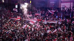 Suporter River Plate mengibarkan bendera saat merayakan gelar juara Copa Libertadores di Obelisk, Buenos Aires, Argentina, Minggu (9/12). River Plate merebut gelar juara Copa Libertadores usai menaklukkan Boca Juniors. (AP Photo/Gustavo Garello)