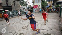 Ekspresi salah satu remaja saat bermain sepak bola di kolong rel kereta kawasan Juanda, Jakarta, Jumat (27/5). Tidak tersedianya ruang terbuka menyebabkan lahan tersebut dijadikan tempat bersosialisasi bagi warga. (Liputan6.com/Immanuel Antonius)