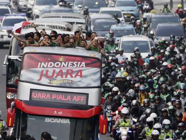 Pemain dan ofisial Timnas Indonesia U-22 menaiki bus tingkat saat konvoi menuju Istana Negara Jakarta, Kamis (28/2). Pawai tersebut untuk merayakan keberhasilan skuat Garuda Muda menjuarai Piala AFF U-22 di Kamboja. (Bola.com/M Iqbal Ichsan)