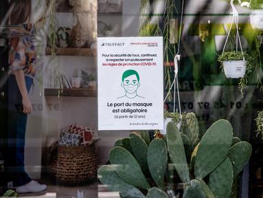 Pengumuman perintah wajib masker di jendela sebuah toko di Paris, Prancis, 20 Juli 2020. Instruksi pemerintah Prancis untuk mewajibkan pemakaian masker mulai berlaku pada Senin (20/7) di tengah munculnya tanda-tanda mengkhawatirkan dari percepatan penyebaran COVID-19. (Xinhua/Aurelien Morissard)