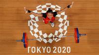 Foto yang diambil dengan kamera robot ini menunjukkan reaksi Windy Cantika Aisah dari Indonesia saat berlaga dalam kompetisi angkat besi 49kg putri pada Olimpiade Tokyo 2020 di Tokyo International Forum, Tokyo pada 24 Juli 2021. (AFP/Pool/Chris Graythen)