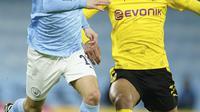 Gelandang Manchester City, Bernardo Silva berebut bola dengan gelandang  Borussia Dortmund, Dortmund Jude Bellingham pada leg pertama perempat final Liga Champions di Etihad Stadium, Rabu (7/4/2021) dini hari WIB. Man City menjungkalkan Dortmund dengan skor 2-1. (AP Photo/Dave Thompson)