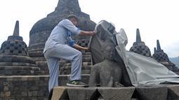 Seorang pekerja menutup stupa di kompleks candi Borobudur, Magelang, Jawa Tengah, Senin (23/11/2020). Penutupan candi Borobudur oleh BKB (Balai Konservasi Borobudur) sebagai langkah antisipasi melindungi batu candi dari abu vulkanik jika Gunung Merapi erupsi. (Photo by Agung Supriyanto/AFP)