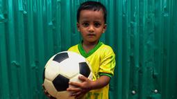 Seorang anak Rohingya mengenakan jersey timnas Brasil sambil memegang bola di kamp pengungsi Kutupalong di Ukhia, Bangladesh, 19 Juli 2018. Bagi pengungsi anak-anak Rohingya, Piala Dunia 2018 ini adalah ajang pertama bagi mereka. (AFP/Munir UZ ZAMAN)
