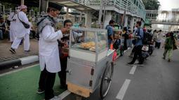 Pedagang makanan melayani pembeli saat berjualan di tengah aksi reuni 212, sekitaran Jalan Medan Merdeka Barat, Jakarta, Senin (2/12/2019). Sejumlah PKL meraup untung dengan berjualan di tengah ribuan massa Persaudaraan Alumni 212 yang mengikuti reuni di Monas. (Liputan6.com/Faizal Fanani)