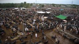 Orang-orang berkerumun di pasar ternak menjelang Hari Raya Idul Adha di Peshawar, Pakistan (13/7/2021). Jelang Idul Adha, Pasar ternak di Peshawar, Pakistan mulai sibuk menjual hewan kurban. (AFP/Abdul Majeed)