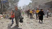 Penduduk sipil Suriah dibantu oleh regu penyelamat helm putih pergi menyelamatkan diri dari Idilib (AFP Photo)