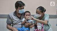 Seorang ibu hamil memberi minum anaknya saat menunggu antrean untuk pemeriksaan rutin di Puskesmas Kecamatan Jatinegara, Jakarta, Kamis (26/11/2020). (merdeka.com/Iqbal S. Nugroho)