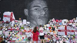 Sejumlah orang tampak menempelkan pesan dukungan dan meletakkan karangan bunga hingga pernak-pernik timnas Inggris di depan mural tersebut. (Foto:AP/Jon Super)
