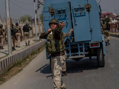 Seorang tentara paramiliter India menggunakan ketapel selama bentrok dengan pengunjuk rasa selama protes terhadap pembunuhan pemberontak di Srinagar, Kashmir yang dikuasai India, (1/4). (AP Photo / Dar Yasin)
