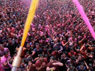 Umat Hindu bersorak ketika bubuk berwarna dan air disemprotkan kepada mereka saat Festival Holi di Kuil Swaminarayan, Ahmedabad, India, Selasa (10/3/2020). Festival Holi menandai datangnya musim semi di India. (AP Photo/Ajit Solanki)