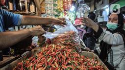 Pedagang melayani pembeli cabai rawit merah di Pasar Senen, Jakarta, Kamis (4/3/2021). Data Ikatan Pedagang Pasar Indonesia (Ikappi) mencatat harga cabai rawit merah saat ini di pasaran berkisar Rp120.000 per kilogram. (merdeka.com/Iqbal S. Nugroho)