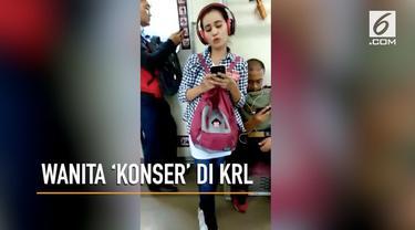 Seorang wanita tanpa sadar bernyanyi dengan suara keras  di KRL Jakarta Kota-Bogor.