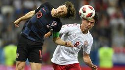 Duel pemain Kroasia, Luka Modric (kiri) dan pemain Denmark, Thomas Delaney pada laga 16 besar Piala Dunia 2018 di Nizhny Novgorod Stadium, Rusia, (1/7/2018). Kroasia menang 3-2 lewat adu penalti. (AP/Martin Meissner)