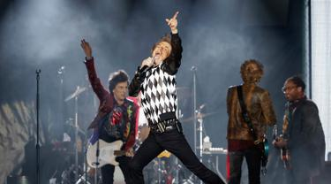 Penampilan Mick Jagger (tengah) saat konser Rolling Stones dalam tur 'No Filter' di Soldier Field, Chicago, Amerika Serikat, Jumat (21/6/2019). Jagger tampil memukau dengan aksinya yang energik di atas panggung. (Kamil Krzaczynski/AFP)