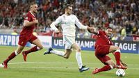 Penyerang Real Madrid, Gareth Bale, berusaha melewati bek Liverpool pada laga final Liga Champions di Stadion NSC Olimpiyskiy, Kiev, Minggu (27/5/2018). Real Madrid menang 3-1 atas Liverpool. (AP/Pavel Golovkin)