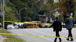 Pejabat setempat meninjau lokasi kecelakaan antara bus komuter dengan bus sekolah di Baltimore, Maryland, Selasa (1/11). Hingga saat ini, otoritas berwenang di Baltimore belum memberikan informasi terkait penyebab kecelakaan. (AP Photo/Patrick Semansky)