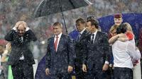 Presiden FIFA Gianni Infantino menutupi kepalanya dengan tangan sementara Presiden Rusia, Vladimir Putin dilindungi payung saat hujan turun selama penyerahan medali dan trofi Piala Dunia 2018 di Stadion Luzhniki, Minggu (15/7). (AP/Matthias Schrader)