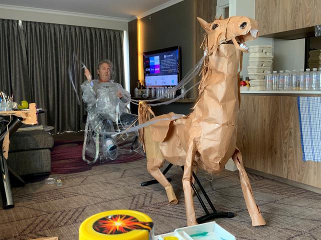 David Marriott berpose dengan kuda kertasnya Russell di kamar hotelnya di Brisbane, Australia, 6 April 2021. Saat berada dalam kamar hotel untuk karantina, direktur seni di iklan TV itu bosan dan mulai membuat pakaian koboi dari kantong kertas makanannya yang dikirimkan. (David Marriott via AP)