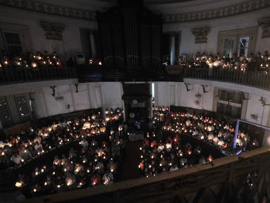 Jemaat memanjatkan doa dengan menyalakan lilin pada Misa Malam Natal di Gereja Immanuel, Jakarta, Senin (24/12). Misa Natal tahun ini mengangkat tema Membangun Spiritualitas Damai yang Menciptakan Perdamaian. (Merdeka.com/Iqbal S. Nugroho)