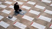 Seorang pria yang mengenakan masker berdoa di sebelah ruang yang telah ditentukan sebelumnya, dengan menerapkan pembatasan sosial yang diberlakukan untuk mencegah penyebaran Covid-19 sebelum salat Idul Fitri, di Masjid Agung Durres, Albania pada 24 Mei 2020. (Photo by Gent SHKULLAKU / AFP)